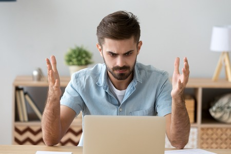 Foto de Frustrated annoying man sitting at the desk in office using computer, looking at broken crashed laptop feels anger and indignance. Worried male has verification password problems or data loss concept - Imagen libre de derechos