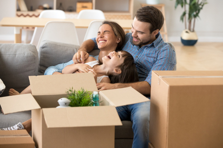 Photo pour Multi-ethnic family spend time together sitting on couch in living room have fun play with little preschool daughter surrounded by cardboard on boxes at home. Buying new house moving mortgage concept - image libre de droit