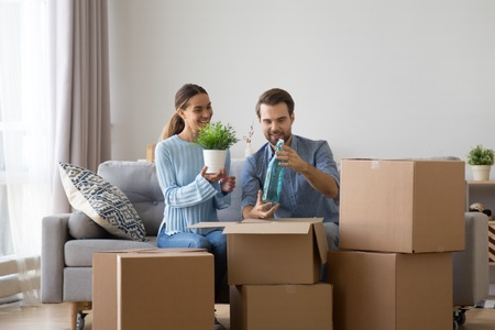 Foto de Married diverse couple sitting together on sofa in living room at new modern home unpack belongings from cardboard boxes wife hold flower pot, husband hold decorative glass bottle. Moving day concept - Imagen libre de derechos