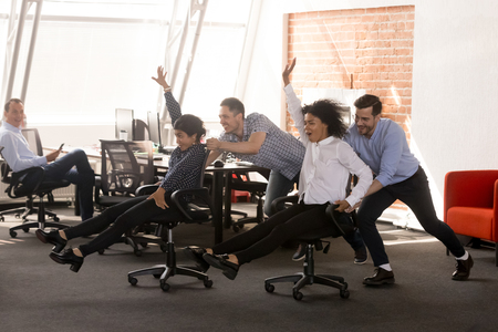 Foto de Carefree excited diverse workers having fun riding oh chairs celebrating friday together, happy employees enjoy funny competition laughing together feel great at work break, friendly office team game - Imagen libre de derechos