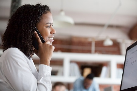 Photo pour Smiling black female employee communicate talking on phone working at pc in office, happy African American woman worker answer call speaking with client or chatting with friends at workplace - image libre de droit