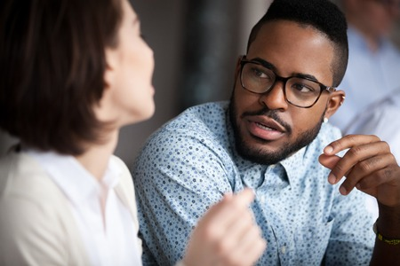 Photo pour Close up of multiracial colleagues chat talking or discussing something in office, black man speak with female coworker negotiating about business project, having conversation. Cooperation concept - image libre de droit