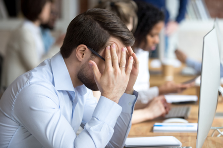 Nervous male employee massage temples worry to finish work till deadline, stressed worker sit in front of computer suffering from headache or migraine, desperate man cope anxiety attack at workplace