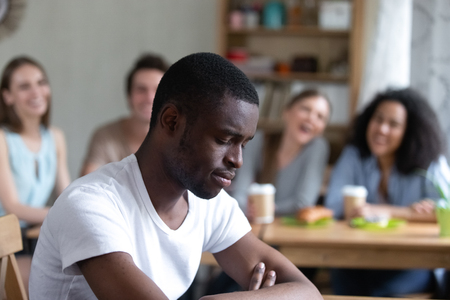 Photo pour Group diverse people sitting in cafe laughing scoffing at black guy. Focus on sitting separately man feels upset and unhappy, schoolmates not take him to their company. Racial discrimination concept - image libre de droit