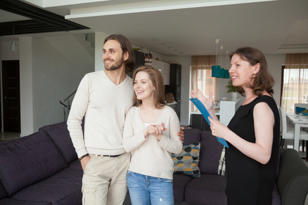 Photo pour Three person standing in living room. Realestate agent, showing property house for sale or tenant to young satisfied married couple. New home, moving and real estate loan and mortgage concept - image libre de droit