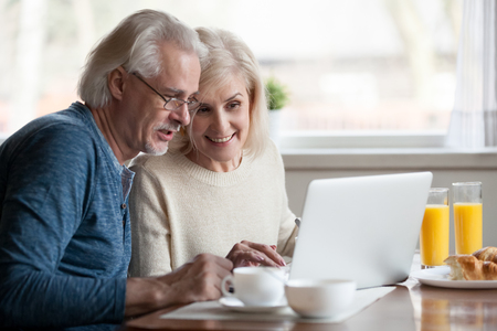 Foto de Aged couple busy look at laptop screen while having delicious breakfast at home kitchen, excited senior man and woman use computer during morning routine, elderly wife show something to husband at pc - Imagen libre de derechos