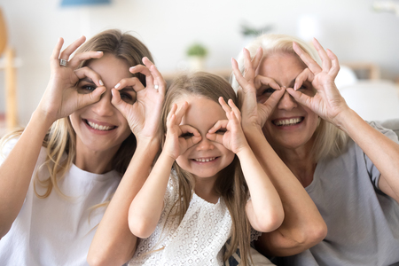 Foto de Happy kid granddaughter, mother and grandmother having fun portrait, cheerful 3 generations women family smiling making funny faces looking at camera, grandma, mom and child grimacing together - Imagen libre de derechos