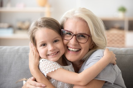 Foto de Happy old grandmother hugging little grandchild girl looking at camera, smiling mature mother or senior grandma granny laughing embracing adopted kid granddaughter sitting on couch, headshot portrait - Imagen libre de derechos