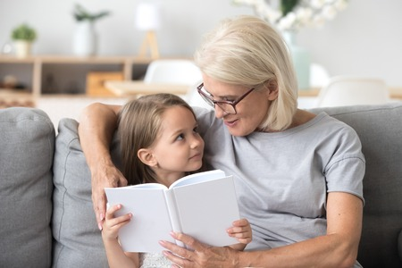 Photo pour Loving grandmother teaching granddaughter holding book sitting on sofa, grandma baby sitter embracing kid girl reading fairytale to cute child, nanny granny telling story to preschool grandchild - image libre de droit