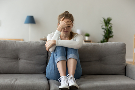 Unhappy female sit on sofa feeling lonely and sad, upset girl crying at home having relationships or life problems, hurt young woman on couch coping with emotions after breakup or bad news