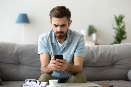 Photo pour Millennial man sit on couch using smartphone shocked by reading online news, surprised male get breaking message or text on mobile phone, confused guy holding cell see virus warning notification - image libre de droit