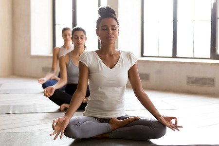 Photo pour Yogi black woman and row of diverse group of sporty people doing yoga Padmasana exercise, Lotus pose, working out indoor, mixed race female students at training studio. Well being, wellness concept - image libre de droit