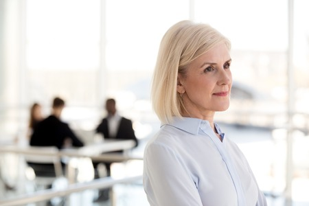 Photo pour Thoughtful dreamy middle aged businesswoman looking away thinking of new goals opportunities in office, serious mature senior old woman planning future, dreaming of success, business vision concept - image libre de droit