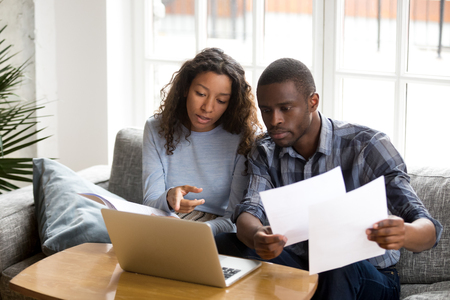 Foto de Serious African American couple discussing paper documents, sitting together on couch at home, man and woman checking bills, bank account balance, terms of contract, mortgage, loan agreement - Imagen libre de derechos