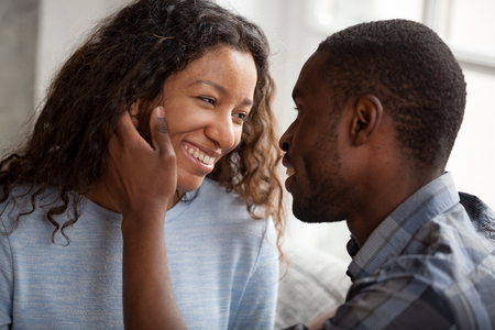 Foto de Happy African American couple having date at home, sitting together on couch, loving man touching attractive smiling woman face with tenderness, looking in eyes to each other, feelings, first kiss - Imagen libre de derechos