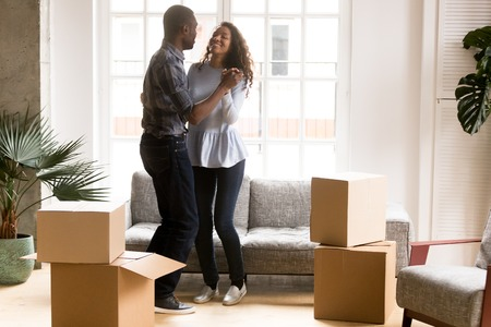 Foto per Happy African American couple in love dancing after moving in new house, attractive smiling woman and man celebrating relocating, cardboard boxes with belongings, homeowners in new apartment - Immagine Royalty Free