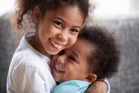Photo pour Happy African American siblings embracing, sitting together on couch at home in living room, little preschooler girl hug toddler adorable boy, good relations between sister and brother, close up - image libre de droit