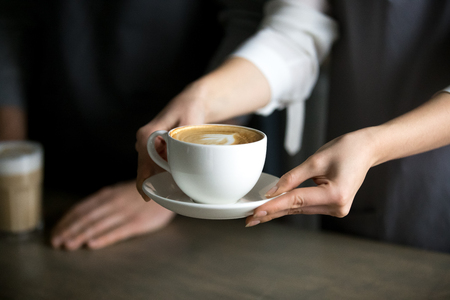 Photo pour Close up of barista holding aromatic cappuccino, serving it to coffeeshop visitor, waitress giving cup of fresh brewed coffee with milk foam to cafe guest, bringing latte drink to coffeehouse table - image libre de droit