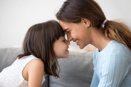 Photo pour Close up profile faces smiling mother and daughter touching with foreheads with closing eyes. Mom expressing understanding candid emotions and love to sweet little child. Happy friendly family concept - image libre de droit