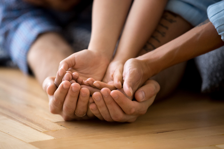 Foto de Family hands palms stacked on warm wooden floor. Mother daughter and father arms close up. Concept of support and love, understanding and devotion, bonding and relatives people warm relationships - Imagen libre de derechos