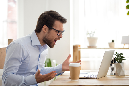 Foto de Mad male worker lose temper scream loudly having computer problems or virus attack, furious man shout experience laptop breakdown or data loss while working, angry employee get error message on pc - Imagen libre de derechos
