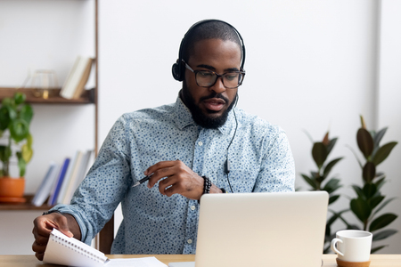 Foto de Black young man sitting at table wearing headphones learn foreign language improves knowledge looking at pc screen listening audio lesson holding pen and notepad makes some notes. E-learning concept - Imagen libre de derechos