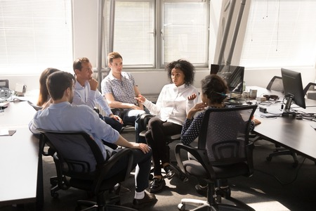 Photo pour Serious African American female leader, coach talking with employees at company meeting, boss discussing business strategy, plan with multiracial team office workers, giving instructions, report news - image libre de droit