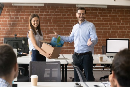 Foto de Excited company leader introducing hired female employee holding cardboard box with belongings in hands, team with ceo welcoming new member, newcomer, first day at work, introduction concept - Imagen libre de derechos