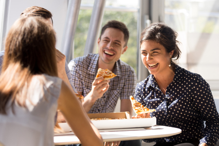 Photo for Indian excited woman laughing at funny joke, eating pizza with diverse colleagues in office, happy multi-ethnic employees having fun together during lunch, enjoying good conversation, emotions - Royalty Free Image
