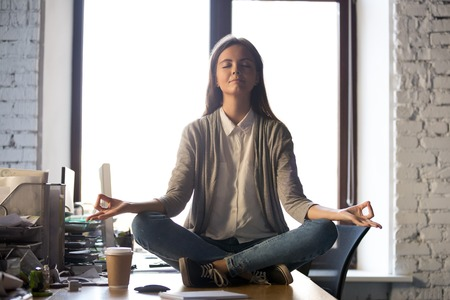 Photo pour Serene calm business woman sit on office desk taking break for meditation, mindful employee doing yoga exercise in lotus pose for relaxation at workplace, no stress relief, balance at work concept - image libre de droit