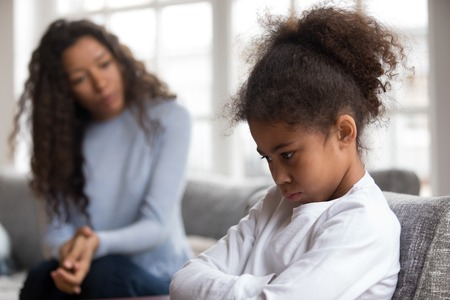 Foto de Mom or psychologist talking counseling upset offended african american child girl feels sad insulted, sulky frustrated black mixed race kid daughter having psychological trauma depression problem - Imagen libre de derechos