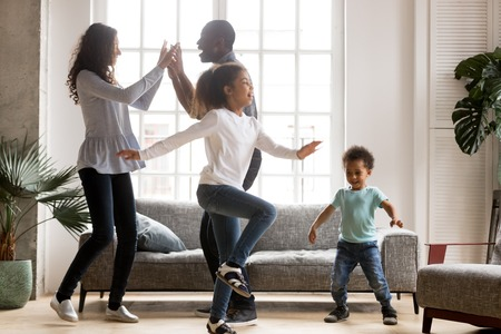Foto de Happy african american family and funny active children having fun dancing together at new home, cheerful black parents and two kids enjoying moving to music spending weekend time in living room - Imagen libre de derechos