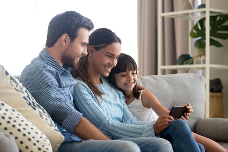 Photo pour Beautiful family of mom dad and little kid child daughter sitting together on sofa smiling looking at smartphone screen taking selfie, making video call or recording vlog with cellphone at home - image libre de droit