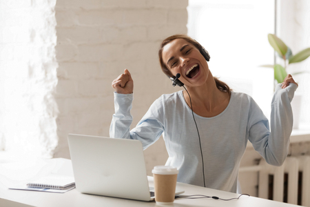 Photo pour Joyful woman in headphones using laptop, sing and dancing during break, moving in rhythm with favorite music, happy female in headset enjoying, studying online, e-learning - image libre de droit