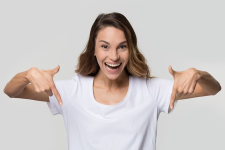 Foto de Happy girl blogger pointing to below fingers down showing subscription like button looking at camera isolated on white blank studio background, excited young woman advertise product portrait - Imagen libre de derechos