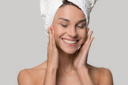 Photo pour Happy woman girl with towel on head smiling touch healthy clean soft moisturized hydrated skin care after applying cream on young face  isolated on white studio background, natural beauty treatment - image libre de droit