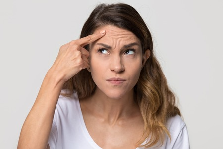 Photo pour Dissatisfied stressed depressed young woman touch forehead worried about skin wrinkle isolated on studio background, cosmetology injection anti aging cream concept, cosmetology facial treatment - image libre de droit