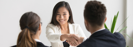 Photo pour Smiling successful young asian applicant handshake with hr manager feels happy getting hired, boss congratulating employee new job employment concept. Horizontal photo banner for website header design - image libre de droit