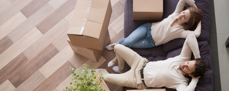 Foto de Horizontal above concept photo married couple at moving day rest relax on couch cardboard boxes on floor feels satisfied breathing fresh air, banner for website header design with copy space for text - Imagen libre de derechos