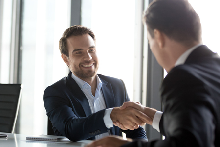 Photo for Happy businessmen in suits shaking hands after successful negotiations at meeting, male partners making business deal or good impression, thanking promising loyalty, respect gratitude handshake - Royalty Free Image
