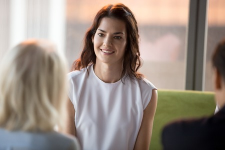 Foto de Confident happy millennial seeker applicant smiling looking at hr during job interview, young smiling businesswoman participating business meeting negotiations, recruiting, first impression concept - Imagen libre de derechos
