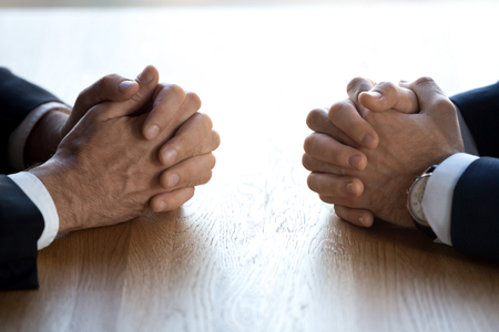 Clasped hands of two business men negotiators opponents opposite on table as politicians dialogue debate, applicant hr job interview, negotiating competitors, rivals confrontation challenge concept