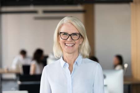Photo pour Cheerful senior businesswoman in glasses looking at camera, happy older team leader ceo manager, female aged teacher professor or mature executive woman mentor smiling in office head shot portrait - image libre de droit