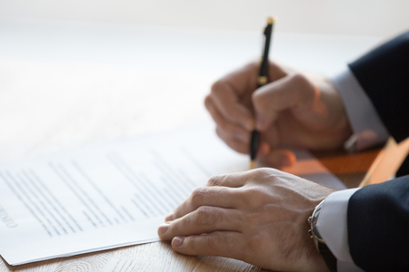 Close up view of male hand signing commercial financial contract concept, businessman put written signature on legal paper filling document form buy insurance, bank services, authorized registration