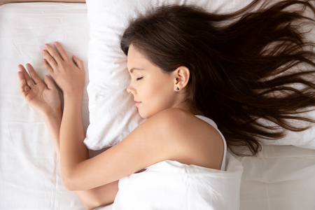 Photo pour Young calm woman sleeping well in cozy comfortable bed lying on soft pillow orthopedic mattress, serene millennial girl resting enough in good healthy sleep nap on white cotton fresh sheets, top view - image libre de droit