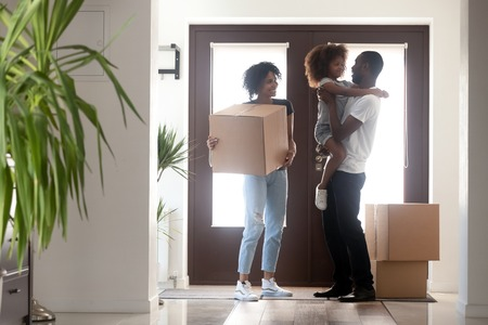 Photo pour Happy black family with kid girl holding box entering into own house on moving day, african american parents and child standing in hallway, mortgage, relocation, tenants welcome to new home concept - image libre de droit