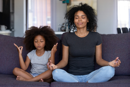 Foto de Mindful african mom with cute funny kid daughter doing yoga exercise at home, calm black mother and mixed race little girl sitting in lotus pose on couch together, mum teaching child to meditate - Imagen libre de derechos