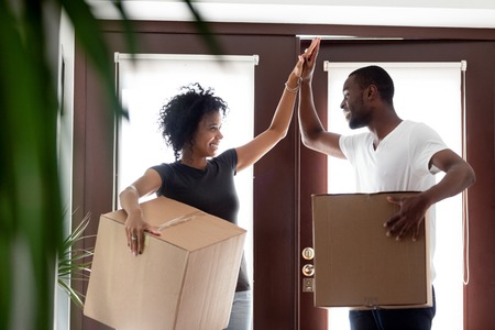 Photo pour Happy young african american couple tenants give high five celebrate moving day in own house hold boxes, excited black family first time buyers owners in new home, mortgage goals, relocation concept - image libre de droit