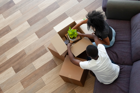 Photo pour Black couple unpacking cardboard boxes in living room moving in out new home, african tenants renters packing stuff preparing for relocation house renovation, removals concept, top view from above - image libre de droit