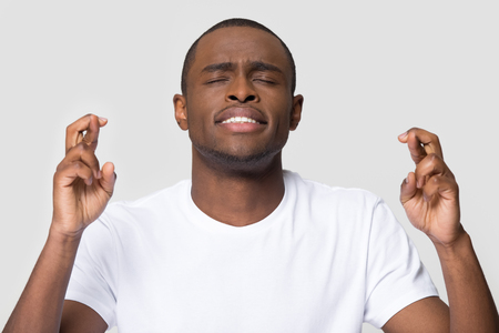 Photo pour Hopeful young african american man crossing fingers wishing for good luck isolated on white blank studio background, funny superstitious black guy student hope for win believe in superstition concept - image libre de droit